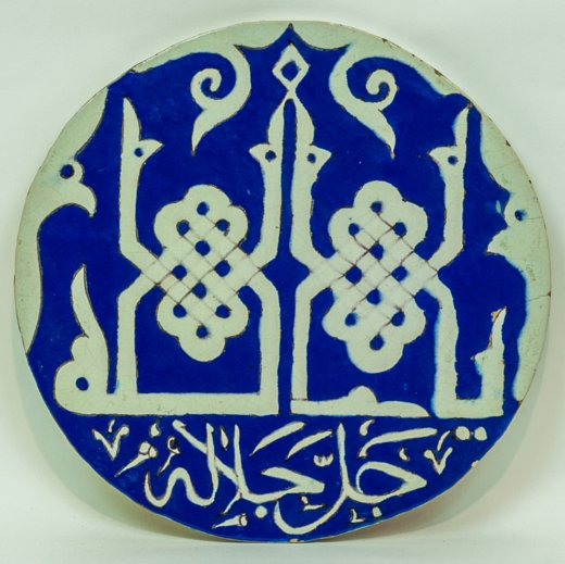 An Islamic round blue and white tile with Arabic writing